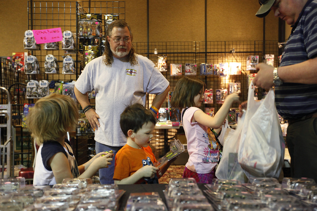 Pat Carrigan, in back with beard, sells toys to from left, Sydney Ivy, Marcus Ivy and their father Mark Ivy at the World of Toys Expo at the Plaza in Las Vegas Friday, Feb. 21, 2014.  (John Locher ...