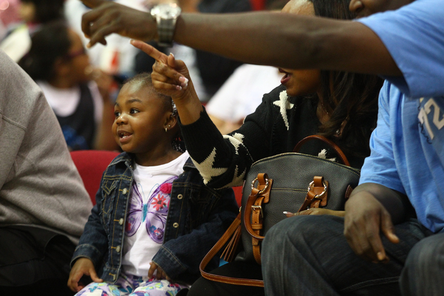Peyton Haynes-Kennedy looks as her grandparents, Calvin and Shawishi Haynes, point out her mom, UNLV's Rmanii Haynes, before the Lady Rebels take on Utah State at the Cox Pavilion in Las Vegas on  ...