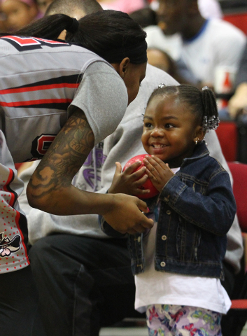 UNLV's Rmanii Haynes hands a small toy basketball to her daughter, Peyton Haynes-Kennedy, 2, before the Lady Rebels take on Utah State at the Cox Pavilion in Las Vegas on Saturday. (Chase Stevens/ ...