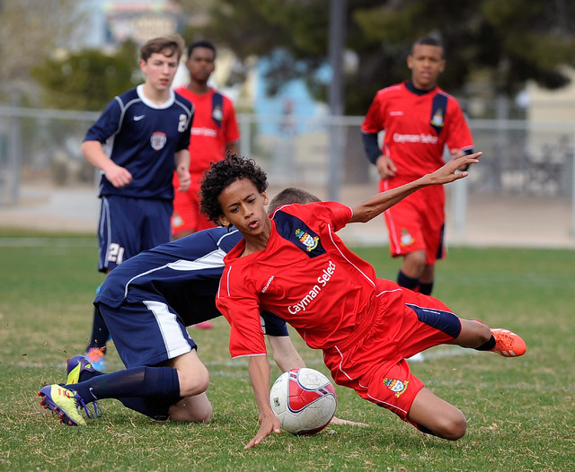 Cayman Select's Ricardo Damasso, right, chases the ball down from Cook Inlet Soccer Club's Dereck Stone during their 14 and under soccer match at Ed Fountain Park on Saturday, Feb. 15, 2014. (Davi ...