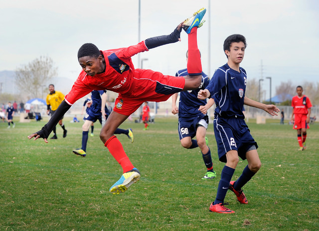 Cayman Select's Louis Gordon, left, is tripped up by Cook Inlet Soccer Club's Tyler Montano during their 14 and under soccer match at Ed Fountain Park on Saturday, Feb. 15, 2014. (David Becker/Las ...