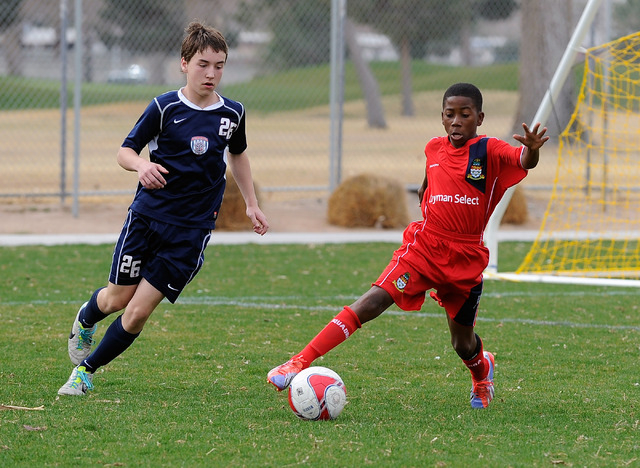 Cayman Select's D'Andre Rowe, right, dribbles the ball from Cook Inlet Soccer Club's Matthew Jones during their 14 and under soccer match at Ed Fountain Park on Saturday, Feb. 15, 2014. (David Bec ...
