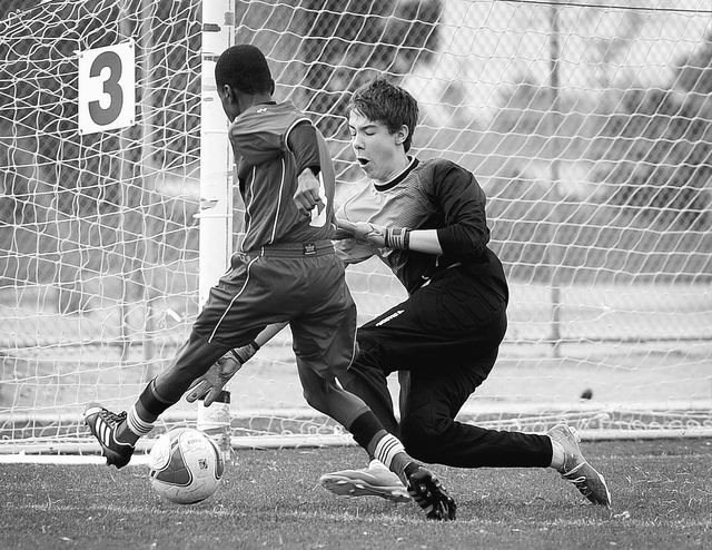 Cayman Select's Kareem Foster, left, takes a shot on goal against Cook Inlet Soccer Club's Elias Colberg during their 14 and under soccer match at Ed Fountain Park on Saturday, Feb. 15, 2014. (Dav ...