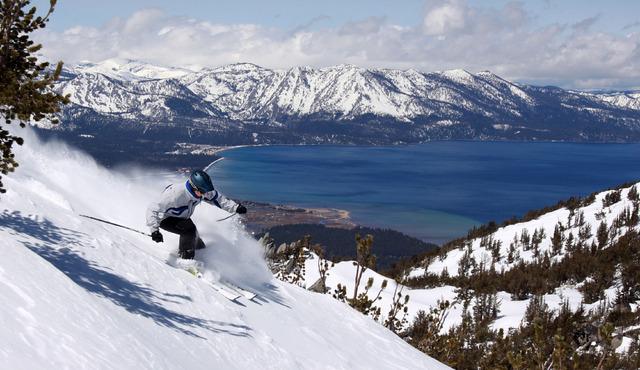 With Lake Tahoe as a backdrop, a skier kicks up some powder in 2010 at Heavenly Ski Resort in South Lake Tahoe, Calif. (AP Photo/Dino Vournas)