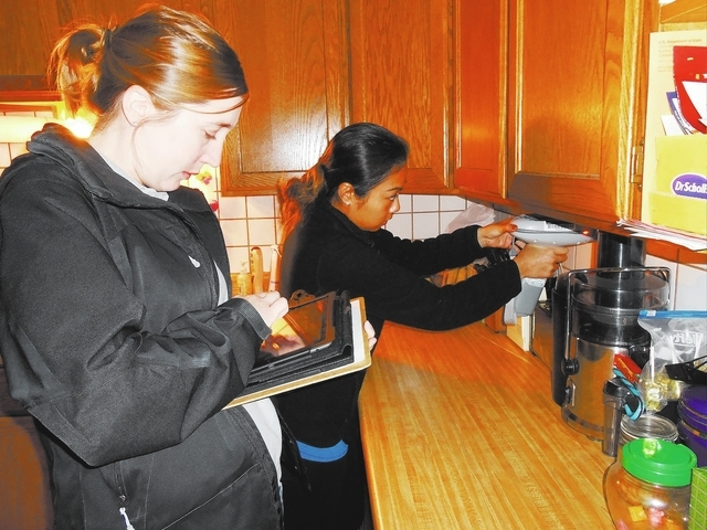 Erin Sheehy, left, and Michelle Ching test to see if lead paint is present at an older Henderson home. (Michael Lyle/ Las Vegas Review-Journal)
