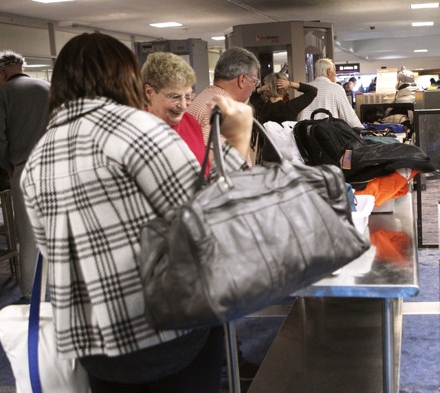 Passengers place their personal items in bins in the TSA screening line at McCarran International Airport in Las Vegas, Dec. 3, 2013. A new program available later this month will allow passengers ...