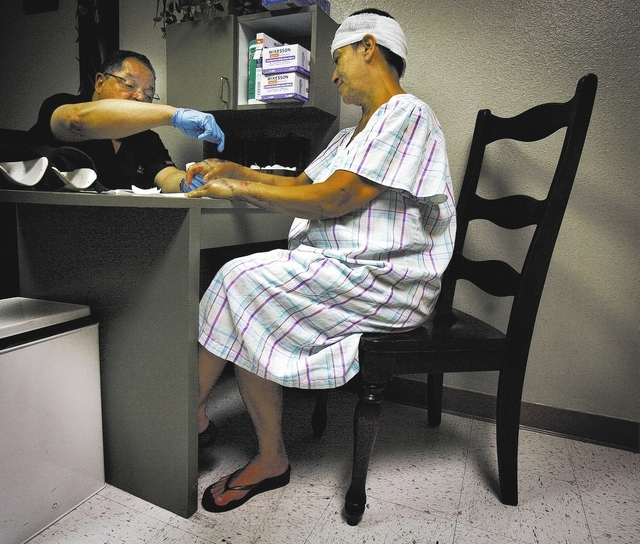Dr. Carl Williams looks at Maria Del Carmen Gomez' surgically repaired hand Friday April  27, 2012.  Gomez, 53, was attack by her former boyfriend with an 18-inch blade outside a convenience store ...