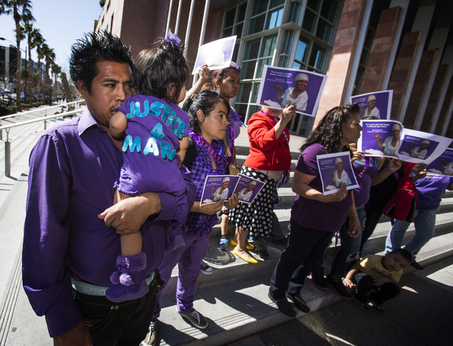 Alejandro Estrada holds his 1-year-old daughter Rudy Estrada during a domestic violence rally to remember Maria Del Carmen Gomez outside Clark County District Court on Monday. On his right is his  ...
