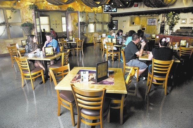 Pictured is the main dining area of the Market Grille Cafe restaurant located at 7070 North Durango Drive in Las Vegas on Saturday, July 6, 2013. Server, Carol Jacobs, serves Pilar and Jason Ahlst ...
