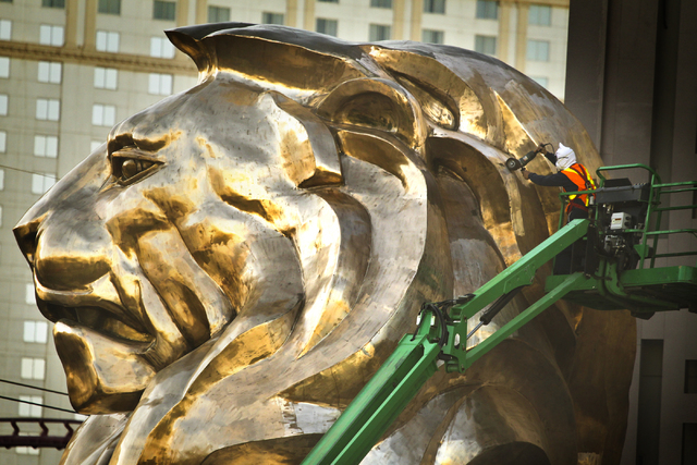 A workman works on the MGM Grand lion statue in front of the hotel in May. MGM Resorts International, which operates 10 resorts on the Strip including MGM Grand, said it reduced its fourth-quarter ...