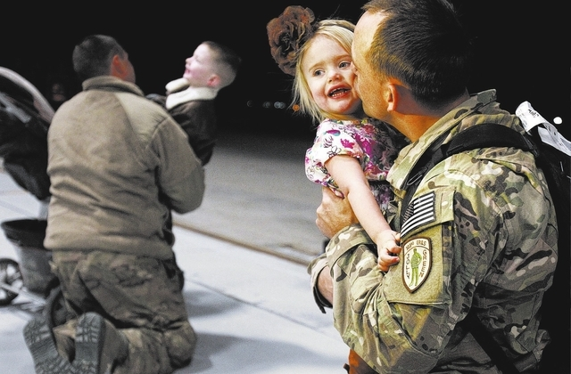 Senior Airman Justin Miller kisses his one-year-old daughter Harper Miller while at Nellis Air Force base Wednesday, Feb. 5, 2014 after he returned from a 4-month deployment to Africa. About thirt ...