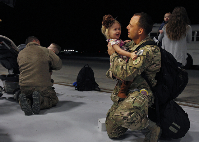 Senior Airman Justin Miller holds his one-year-old daughter Harper Miller while at Nellis Air Force base Wednesday, Feb. 5, 2014 after he returned from a 4-month deployment to Africa. About thirty ...