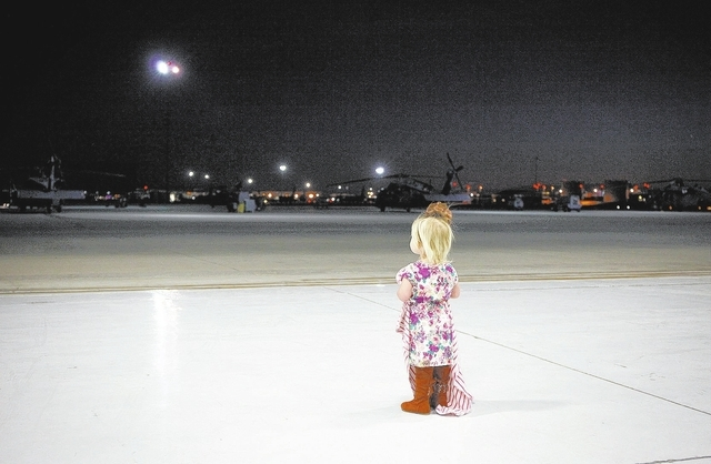 One-year-old Harper Miller waits for her father Senior Airman Justin Miller at Nellis Air Force base Wednesday, Feb. 5, 2014 to greet him home from a 4-month deployment to Africa. About thirty air ...