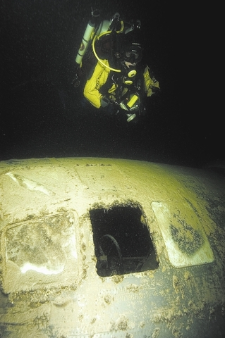 A diver wearing a mixed-gas rig swims over the cockpit of a B-29 Superfortress as it rests at a depth of 170 feet below the surface of Overton Arm of Lake Mead on Feb. 28, 2006. The World War II-e ...