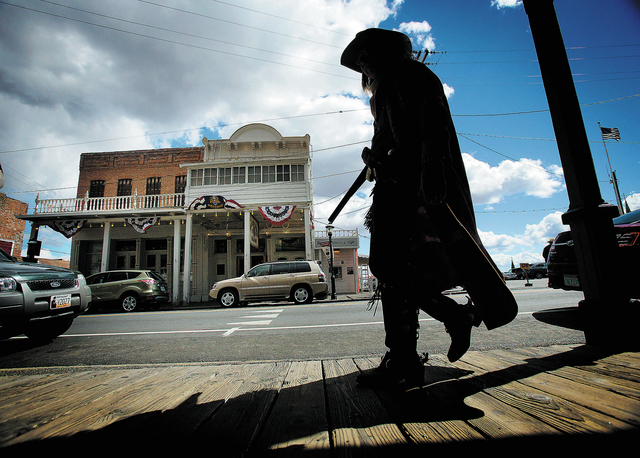 A man dressed in period clothes walk  C Street in Virginia City, Nev., Wednesday, Sept 25, 2013. The county seat of Storey County, Nevada sprang up as a boomtown when silver was discovered on top  ...