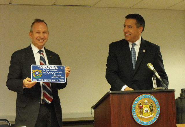 Delaware Gov. Jack Markell holds a souvenir Nevada sesquicentennial license plate, presented to him by Nevada Gov. Brian Sandoval at a signing ceremony for an online poker agreement between the tw ...
