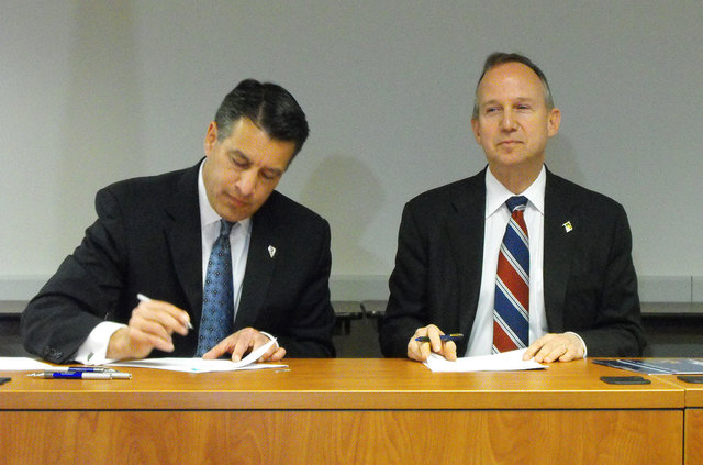 Nevada Gov. Brian Sandoval, left, and Delaware Gov. Jack Markell sign an agreement Tuesday morning in Wilmington, Del., that joins the states in a partnership for online poker. (Steve Tetreault/St ...
