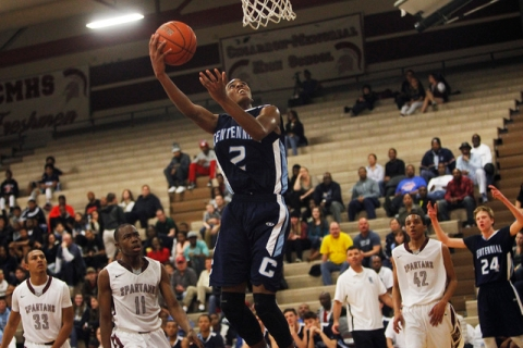 Centennial freshman Troy Brown (2) drives to the hoop in a game against Cimarron-Memorial ea ...