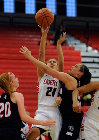 Liberty's Kaily Kaimikaua (21) shoots over Coronado's Karlie Thorn (20) and Kayla Watterson on Tuesday. Kaimikaua finished with eight points in an 82-37 Liberty win. (David Becker/Las Vegas Review ...