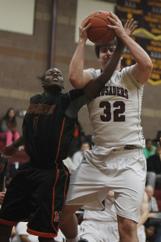 Mojave's Melvin Irvey (1) tries to steal the ball from Faith Lutheran's John Molchon (32) on Thursday. Irvey had 17 points and three steals in a 57-46 Mojave victory. (Jason Bean/Las Vegas Review- ...