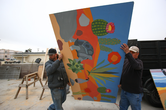 Brian Weaver, left, and Mike Mount, of Weaver Construction, carry a piece of plywood at the unveiling of a new program where vacant and abandoned homes will be fitted with painted plywood panels a ...