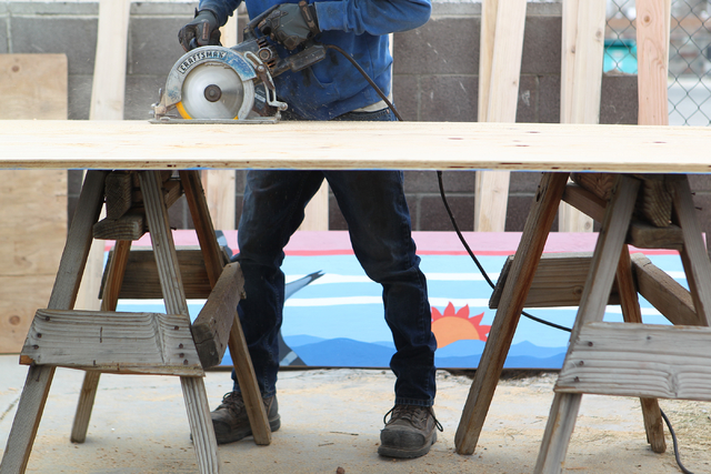 Josh Weaver of Weaver Construction saws a plywood board at the unveiling of a new program where vacant and abandoned homes will be fitted with painted plywood panels, at a home at 106 Shiloah Driv ...