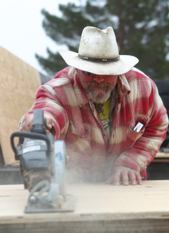 Joe Weaver of Weaver Construction saws a plywood board during the unveiling of a new program where vacant and abandoned homes will be fitted with painted plywood panels, at a home at 106 Shiloah D ...