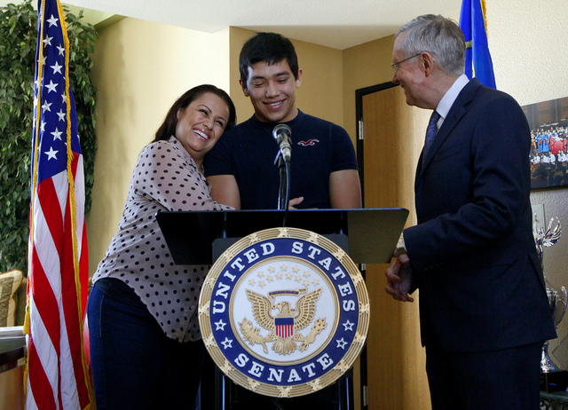 Edith Fawkes, left, hugs her son, Brahyam Zurcher, 17, center, at a press conference held by  Senate Majority Leader Harry Reid, D-Nev., right, at the Latin Chamber of Commerce office in Las Vegas ...