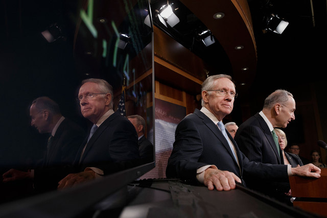 Senate Majority Leader Harry Reid of Nevada, left, listens as Sen. Charles Schumer, D-N.Y., speaks during a news conference Thursday on Capitol Hill in Washington. On a largely party-line vote of  ...