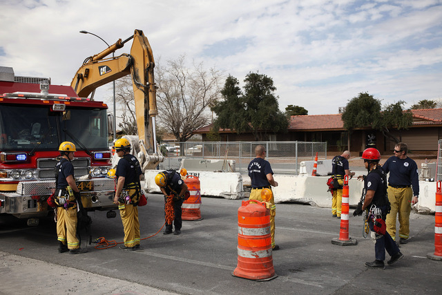 Las Vegas firefighters pack up their equipment after rescuing a worker who was trapped in a trench on Vegas Drive near Michael Way on Wednesday. (John Locher/Las Vegas Review-Journal)