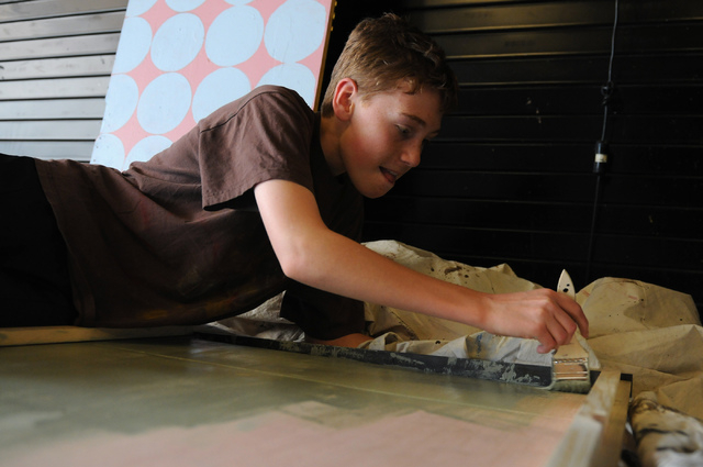 """Sophomore Connor Wright, backstage crew member, paints a door for the upcoming play """"Bye Bye Birdie"""" at the Bishop Gorman High School, Feb. 4. (Erik Verduzco/View)"""