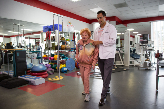 Sylvia Duboys, left, and Anthony Tabor, a doctor of physical therapy, walk during Duboys' session at the Keith Kleven Institute, Jan. 30. (Samantha Clemens/View)