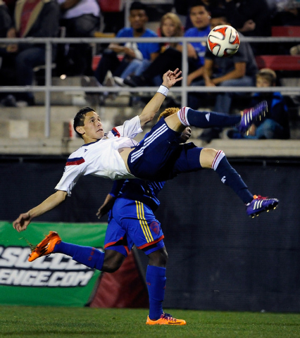 Chivas USA's Eric Avila uses a bicycle kick to get the ball pass Colorado's Charles Eloundou and up field during the first half of a preseason MLS match at Sam Boyd Stadium on Sunday, Feb. 16, 201 ...