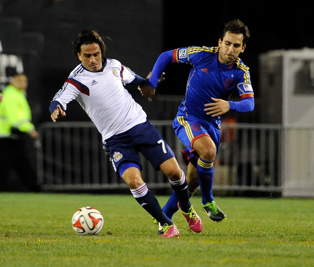 Chivas USA's Mauro Rosales, left, and Colorado's Juan Gusman chase the ball during a preseason MLS match at Sam Boyd Stadium on Sunday, Feb. 16, 2014. (David Becker/Las Vegas Review-Journal)