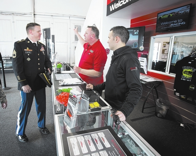 U.S. Army Sgt 1st Class Bradley Melton listens while Mark Daddario and David Perisset, co-founder of Exotics Racing, check him in at the track Feb. 3. Melton visited the attraction as part of his  ...