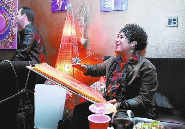 "Areeya Marie Sharpe pauses while painting to watch the ""Wonderground"" variety show at The Olive. She said she is inspired by the kinetic energy at the performance. ""There's energy all arou ..."