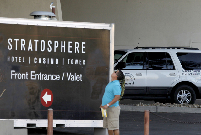 A man looks up to the top of the Stratosphere in front of a Clark County Coroner's Office vehicle on Wednesday. Police are investigating a possible suicide near the Stratosphere. (Justin Yurkanin/ ...