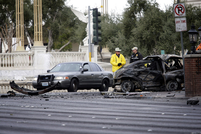 Las Vegas police investigate a charred taxi that exploded upon impact in a crash involving two luxury cars and a shooting incident on the Strip on Feb. 21, 2013. (Jessica Ebelhar/Las Vegas Review- ...