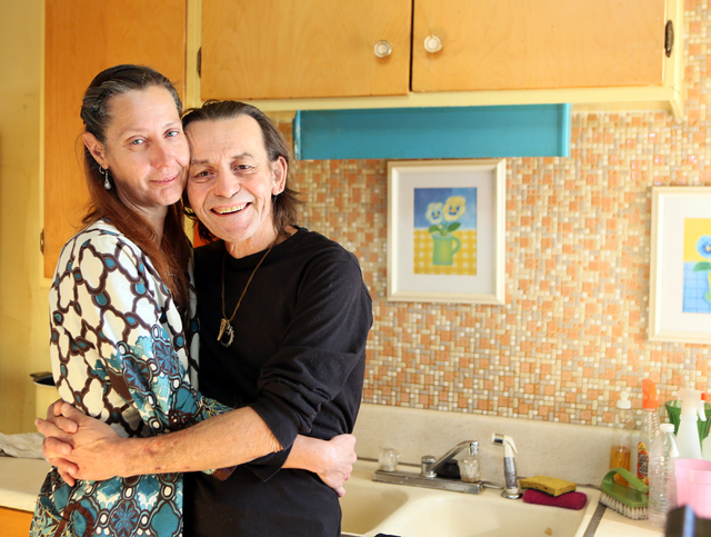 Monica Gamble, left, embraces her husband, William, in their kitchen, Jan. 19. They will celebrate their 30th anniversary in March. (Ronda Churchill/View)