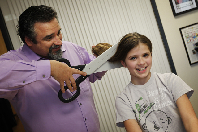Imagine Communications senior partner and creative director Alex Raffi, left, pretends to cut his daughter Elli's hair with a pair of prop scissors in his office in Henderson, Feb. 11. Raffi and h ...