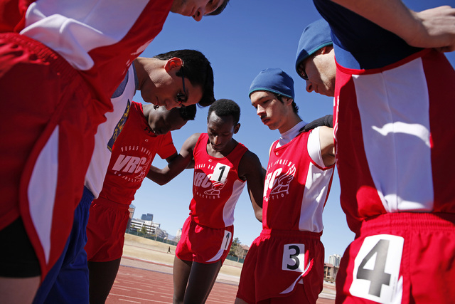 Coach Jake Mazone, right, leads the Vegas Running Connection team in prayer before competing in a run at the Winter All Comers Track & Field meet at UNLV, Feb. 1. The team's goal is to send runn ...