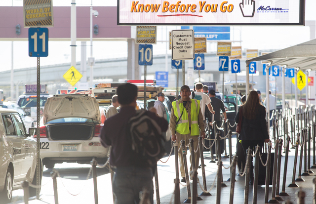 McCarran International Airport passengers get in line for taxicabs at Terminal 1 in Las Vegas on Friday, Jan. 17, 2014. The Nevada Taxicab Authority and McCarran International Airport have put up  ...