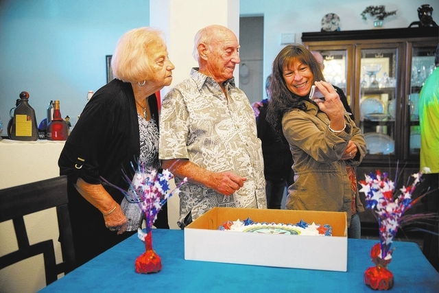 Jay Petrelli (cq), left, and Calvin Pascetta (cq), center, look at a photo Deborah Grattan (cq) took during Pascetta's 90th birthday inside his North Las Vegas home Monday, Feb. 3, 2014. (Samantha ...