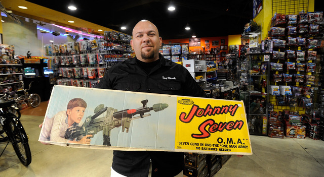 Toy Shack owner Johnny Jimenez displays one of his favorite toys, a 1960s-era Johnny Seven OMA, or One Man Army, toy gun still in its original box, at the Toy Shack at Neonopolis. He said toy coll ...