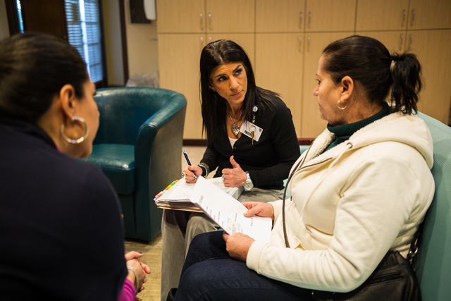 Social work supervisor Susan Shapiro, center, with Nora Luna, director of diversity and education, left, translating, talk with Bertha Guzman, whose sister is a patient, at the Nathan Adelson Hosp ...