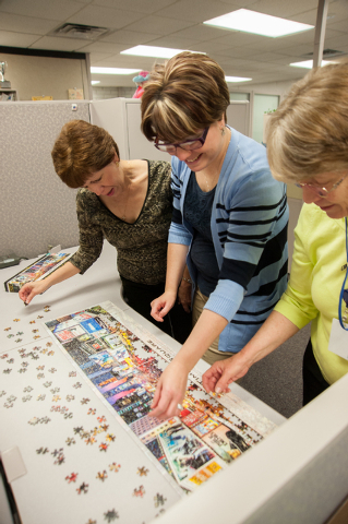 One Nevada Credit Union employees, from left, Nelly Hutchinson, Anna Trevino, and Kathy Lewallen, put the office puzzle together inside the One Nevada Credit Union home offices in Las Vegas, Thurs ...