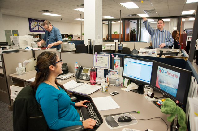 One Nevada Credit Union employee Sara Suniga, bottom left, watches fellow employee Steve O'Donnell toss a golf ball to another employee during a fun moment inside their workplace at the One Nevada ...