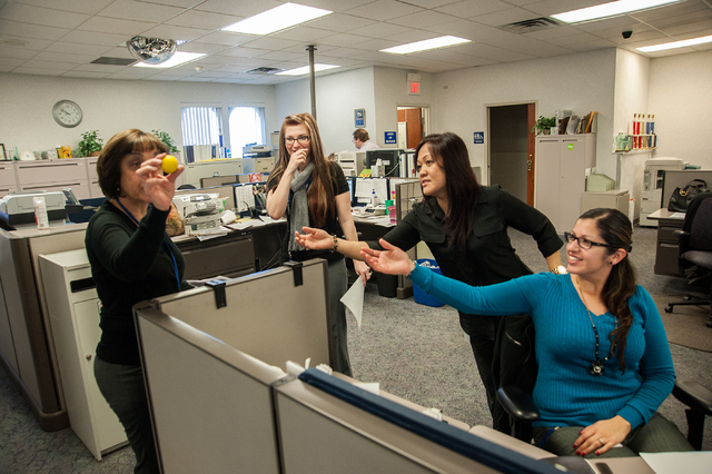 One Nevada Credit Union employees, from left, Maria Dlouhy, Michelle Todd, Beth Hayes, and Sara Suniga play around by tossing a golf ball with other employees inside the workplace at the One Nevad ...