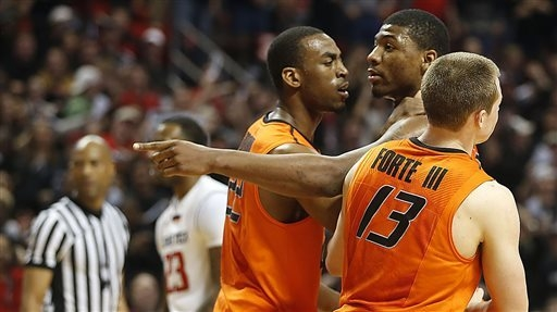 Oklahoma State's Markel Brown (22) and Phil Forte (13) hold Marcus Smart after Smart shoved a fan during their NCAA college basketball game in Lubbock, Texas, on Saturday. (AP Photo/Lubbock Avalan ...
