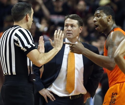 Oklahoma State guard Marcus Smart speaks to the referee alongside coach Travis Ford after Smart shoved a fan Saturday at Lubbock, Texas, in the final seconds of a 65-61 loss to Texas Tech. He was  ...